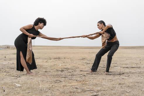 Two women pulling a cloth in bleak landscape - ERRF01957