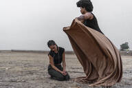 Woman covering another woman with blanket in bleak landscape - ERRF01969