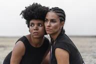 Portrait of two women head to head in bleak landscape - ERRF01975