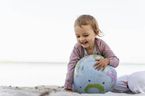 Portrait of happy little girl playing with  Earth beach ball - DIGF08832