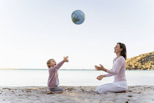 Happy little girl sitting with her mother on the beach playing with Earth beach ball - DIGF08835