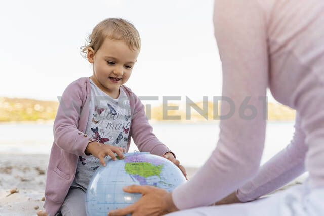 Portrait of little girl looking at Earth beach ball - DIGF08838 - Daniel Ingold/Westend61