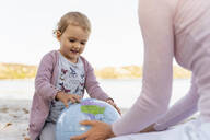 Portrait of little girl looking at Earth beach ball - DIGF08838