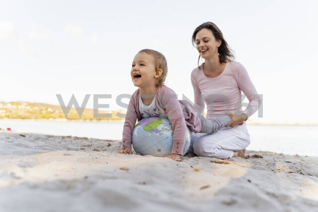 Mother and little daughter playing together with Earth beach ball at seashore - DIGF08841 - Daniel Ingold/Westend61