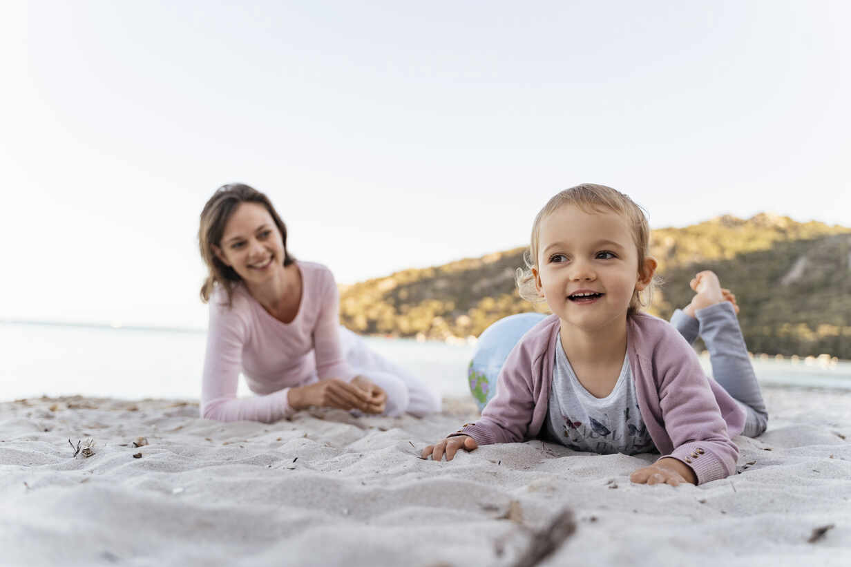 Portrait of smiling little girl on the beach with mother watching her from the background - DIGF08847 - Daniel Ingold/Westend61