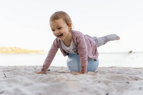 Portrait of laughing little girl balancing on  Earth beach ball - DIGF08850