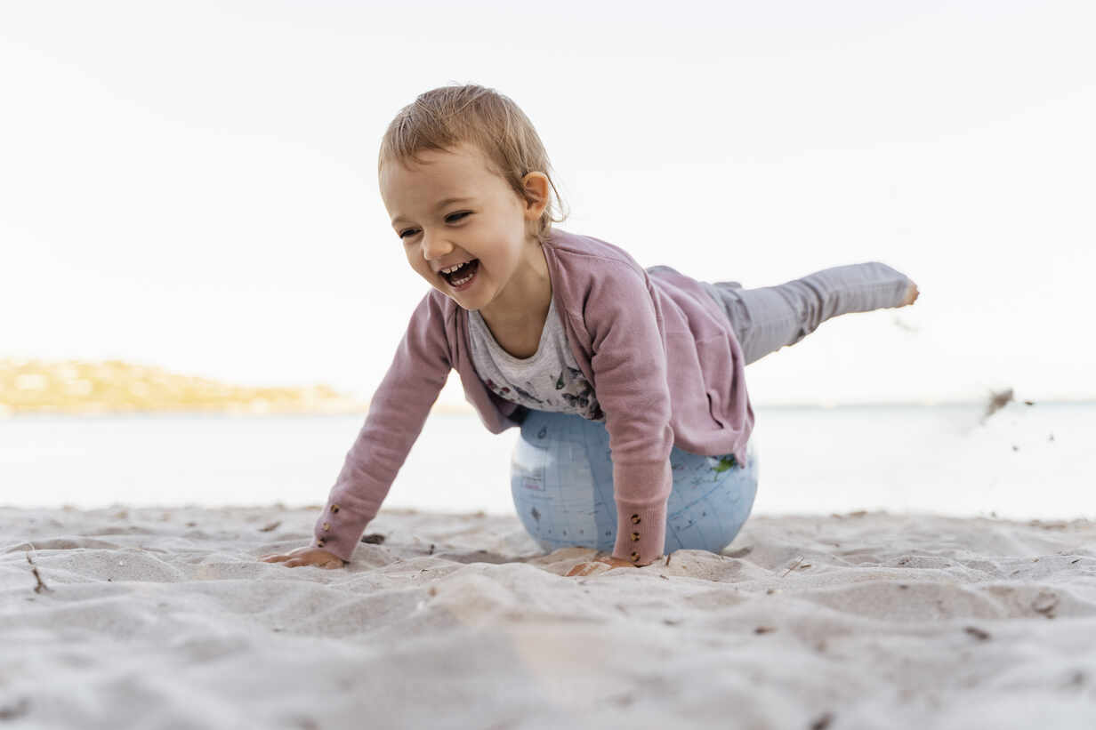 Portrait of laughing little girl balancing on  Earth beach ball - DIGF08850 - Daniel Ingold/Westend61