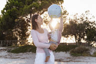 Mother and little daughter playing together with Earth beach ball at sunset - DIGF08853