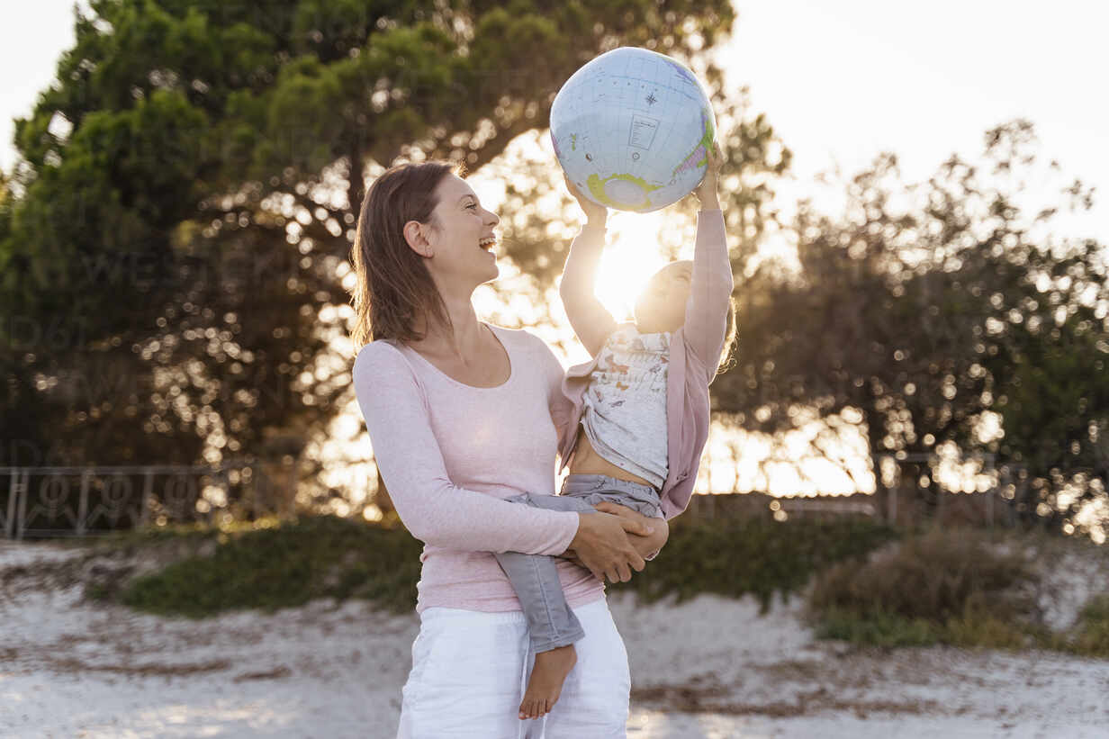 Mother and little daughter playing together with Earth beach ball at sunset - DIGF08853 - Daniel Ingold/Westend61