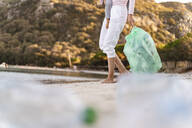 Woman on the beach with little daughter on her arm collecting empty plastic bottles - DIGF08856