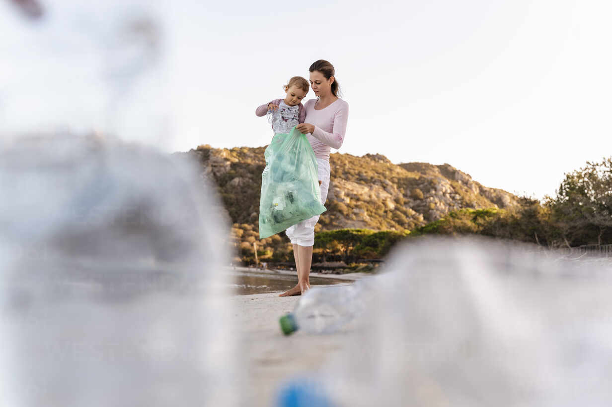 Mother and little daughter collecting empty plastic bottles on the beach - DIGF08859 - Daniel Ingold/Westend61