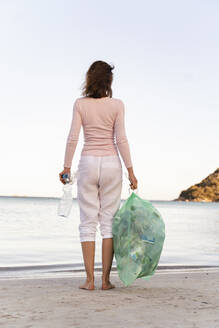 Back view of woman standing on the beach with bin bag of collected empty plastic bottles - DIGF08865