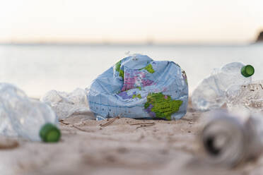Deflated earth beach ball between empty plastic bottles on the beach - DIGF08868