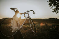 Man carrying a racing cycle in the sunshine - MKF00003