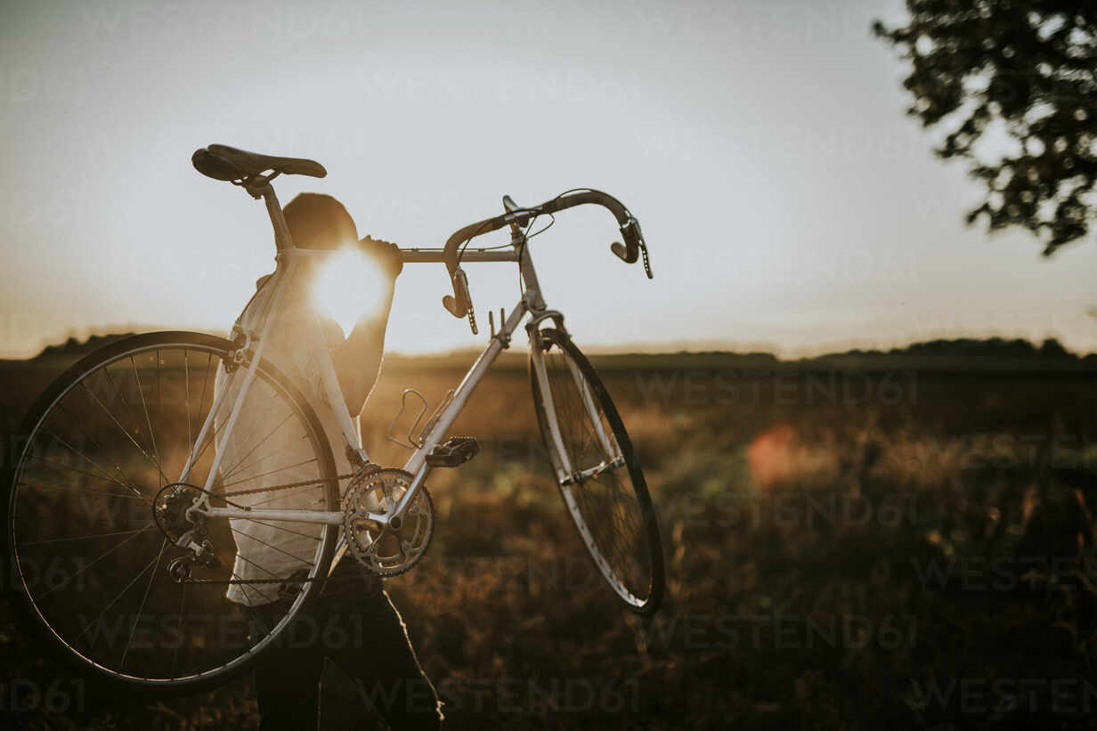 Man carrying a racing cycle in the sunshine - MKF00003 - Markus Kayl/Westend61