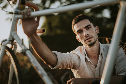 Portrait of a pensive young man with his bicycle outdoors - MKF00006
