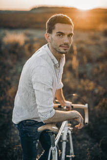Portrait of a young man with his racing bicycle in sunshine - MKF00009