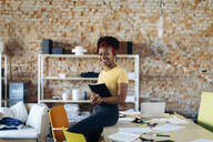 Portrait of confident young woman at table in office holding notebook - SODF00115