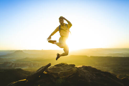 Full length of excited hiker jumping on mountain at Canyonlands National Park - CAVF68204
