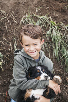 Boy playing with his Bernese mountain dog in the garden - HMEF00671
