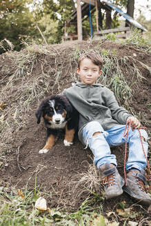 Boy playing with his Bernese mountain dog in the garden - HMEF00674