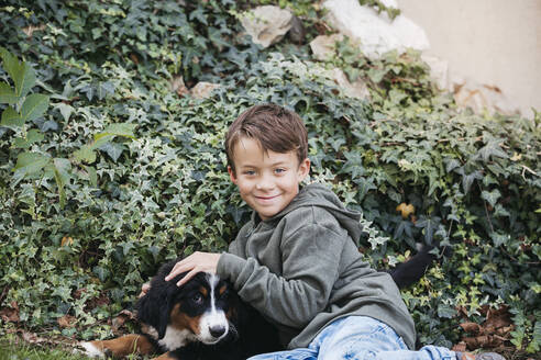 Boy playing with his Bernese mountain dog in the garden - HMEF00677