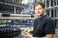 Portrait of confident worker with tablet in factory warehouse - WESTF24271