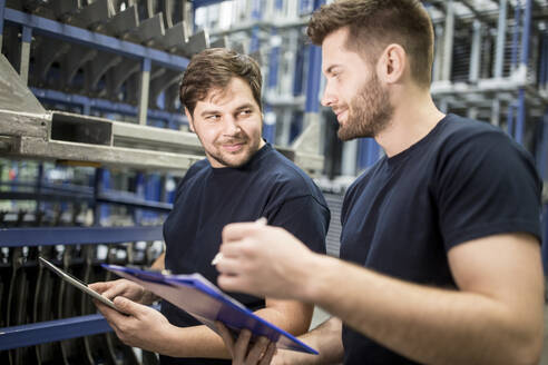 Two workers with clipboard and tablet in factory warehouse - WESTF24274