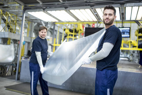 Two colleagues carrying bonnet in car factory - WESTF24286