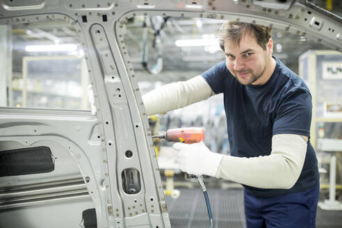 Portrait of confident man working in modern car factory - WESTF24325