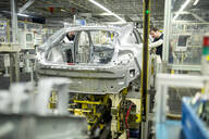 Two colleagues working in modern car factory - WESTF24331