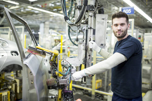 Portrait of confident worker in modern car factory - WESTF24334