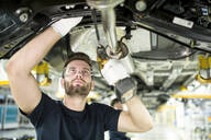 Man working at car underbody in modern factory - WESTF24340