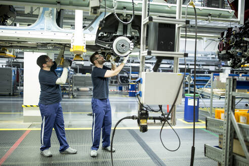 Two colleagues working at car underbody in modern factory - WESTF24349