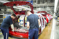Two colleagues working in modern car factory - WESTF24355