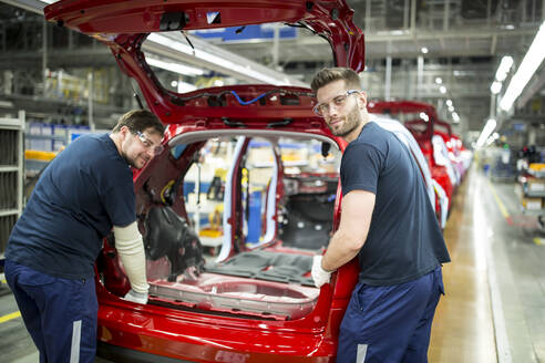 Two colleagues working in modern car factory - WESTF24358