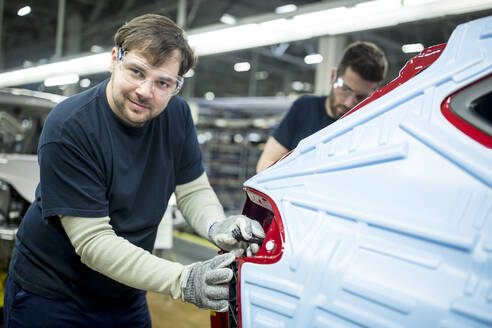 Portrait of confident man working in modern car factory - WESTF24361