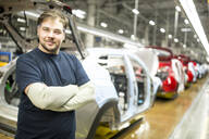 Portrait of confident worker in modern car factory - WESTF24370