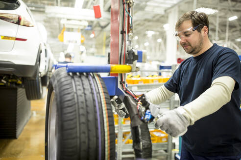Man working on tyre in modern car factory - WESTF24382
