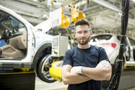 Portrait of confident worker in modern car factory - WESTF24385