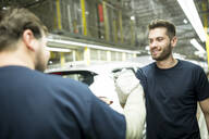 Two colleagues shaking hands in modern car factory - WESTF24388