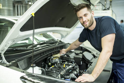Portrait of confident man working on car in modern factory - WESTF24391