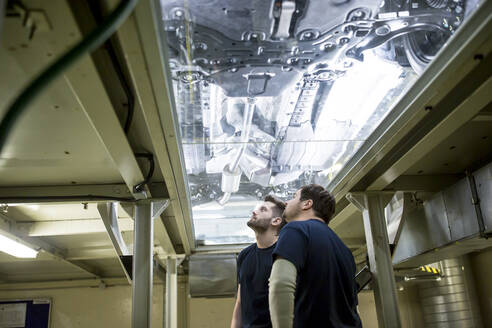 Two colleagues in factory checking underbody of a car - WESTF24394
