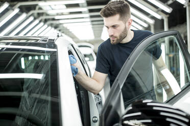 Man working in modern car factory wiping finished car - WESTF24403