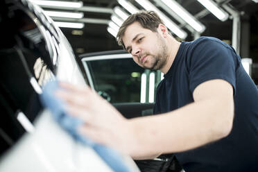 Man working in modern car factory wiping finished car - WESTF24406