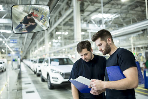 Two colleagues working in modern car factory using clipboard and tablet - WESTF24412
