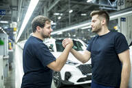 Two colleagues shaking hands in modern car factory - WESTF24415