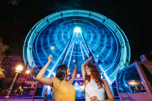 Two friends with sparkles in front of illuminated big wheel at night - MTBF00086