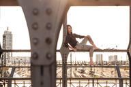 Young woman sitting on Hacker bridge at sunset, Munich, Germany - WFF00126