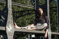 Young woman enjoying the evening sun, sitting on a bridge - WFF00129